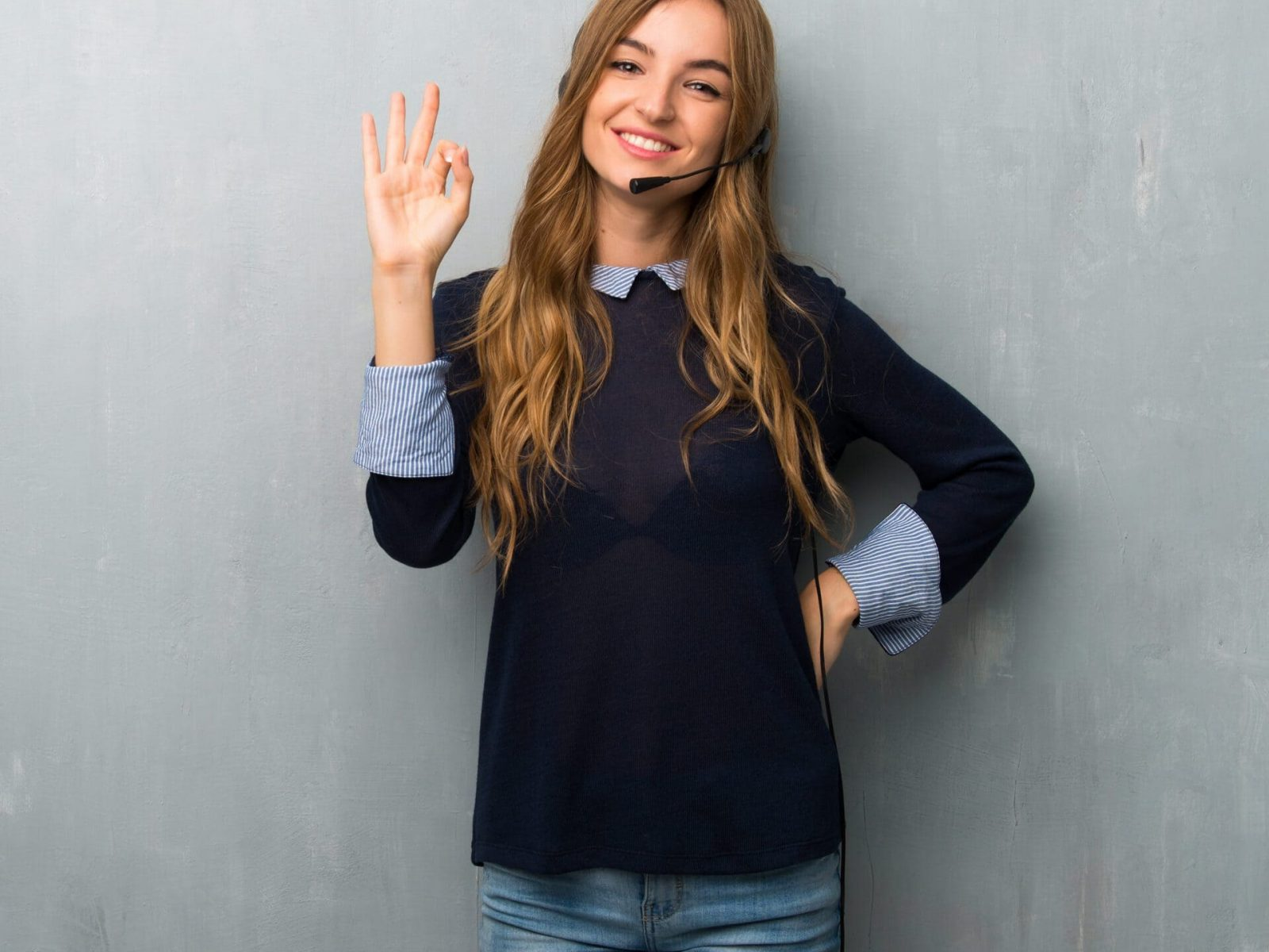 Telemarketer woman showing an ok sign with fingers
